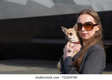 pretty woman in sunglasses with small chihuahua in hands