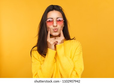 Pretty woman in sunglasses and yellow clothes touching cheeks and looking at camera.