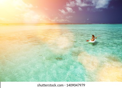Pretty woman swimming in canoe and relax in the sea. Happy island lifestyle. White sand, crystal-blue sea of tropical beach. Vacation at Paradise. Ocean beach relax, kayaking, travel to Maldives