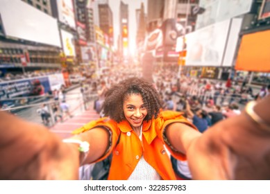 Pretty woman taking a selfie at Times Square, New York - Afroamerican girl taking a memorable self portrait with smartphone while traveling in a crowded city