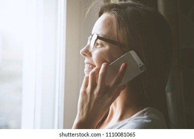 pretty woman talking on phone near window at home