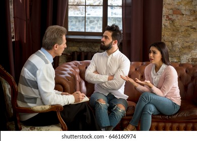 Pretty woman telling psychology about problems existing in her family while her husband sitting with crossed or folded hands and looking away at psychologist's office.