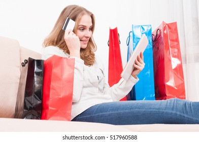 Pretty woman thinking and shopping online holding credit or debit card with bags around like home leisure online shopping