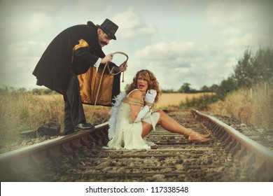 Pretty woman tied up on railway line by classic villain