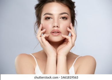 pretty woman touching face with arms and looking to camera, beauty portrait of female with perfect face and nude manicure