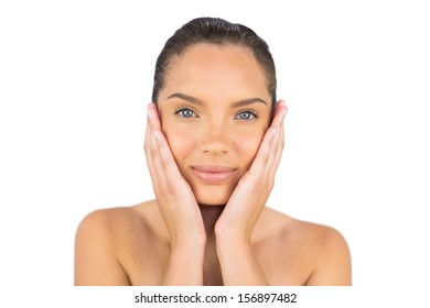 Pretty woman touching her face against white background