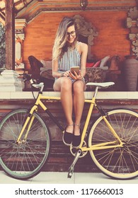 Pretty woman using cellphone while holding old bicycle outdoors.
