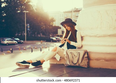 Pretty woman using smartphone, hipster girl, close up portrait, fashion model, hat, street photo, bag, travel backpack, beauty female, touch screen, holding, internet, maps