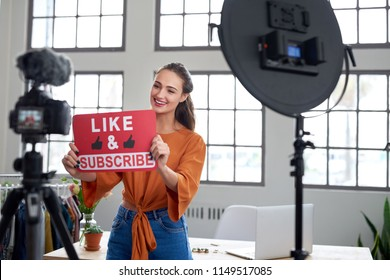 Pretty woman vlogger recording video for her channel using professional camera equipment