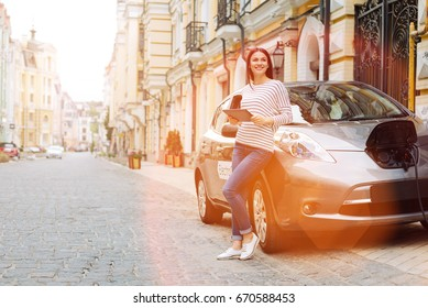Pretty woman waiting while her car charging