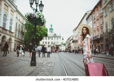 Pretty woman walking around with red suitcase