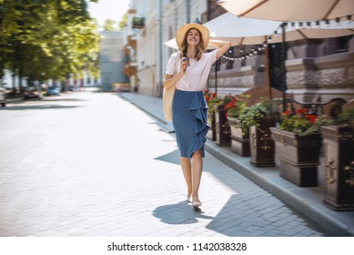 Pretty woman walking down the street with funny mood. She enjoying summer and having fun and joy. She smiling and dancing, holding a cup of morning coffee