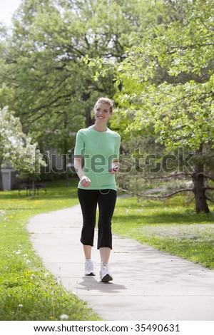 Pretty woman walking in the neighborhood listening to music on her MP3 player
