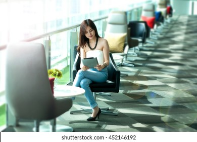 Pretty woman wear blue jeans using tablet at rest area,public place,lens flare effect added