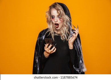 Pretty woman wearing black costume and halloween makeup holding smartphone isolated over yellow background