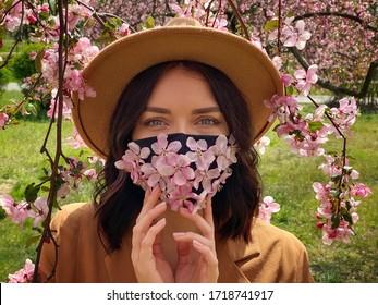 Die hübsche Frau trägt eine Blumenmaske, Frühlingszeit während einer Korona-Virus-Pandemie.