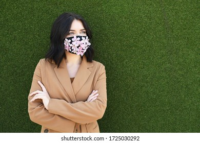 Pretty woman is wearing decorated with flowers face mask on green background