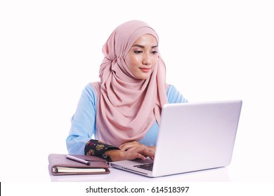 Pretty woman wearing hijab in front of laptop search and doing office work isolated in white background - office, business, finance and work station concept