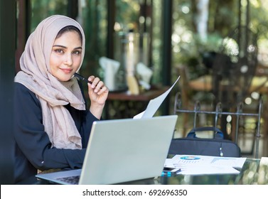 Pretty woman wearing hijab in front of laptop search and doing office work, business, finance and workstation concept.