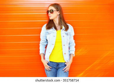 Pretty woman wearing a sunglasses and jeans jacket in profile over orange background, looking away