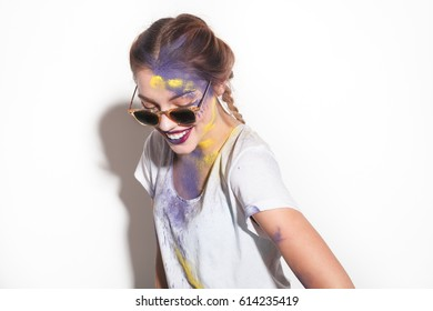 Pretty woman wearing sunglasses with yellow and purple Holi colors on face.