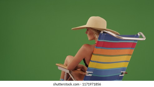 Pretty woman wearing sunhat sitting in beach chair on green screen