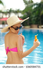 Pretty woman wearing swimming suit and hat with wide flaps sitting at outdoor swimming pool and applying sunscreen on her shoulder, portrait shot