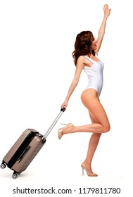 Pretty woman wearing white swimsuit and standing with travel bag, isolated on white background