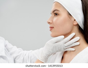 Pretty woman with well groomed skin receiving inspecting of face in medical centre. Patient in white bathrobe posing, looking away. Hands of doctor in white rubber gloves touching neck, examining.
