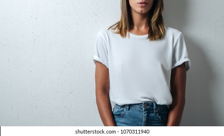 Pretty woman in white blank t-shirt, grunge wall, studio close-up