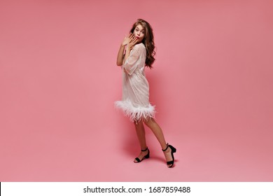 Pretty woman in white dress covers her mouth. Surprised girl in good mood poses on pink isolated background.