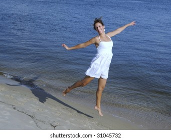 pretty in woman in white dress jumping in the sand at the beach