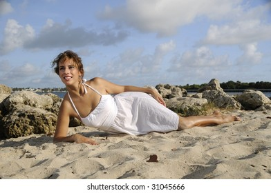 pretty woman in white dress, in the sand at the beach