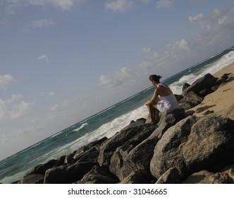 Pretty woman in white dress sitting on rocks watching the ocean