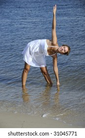 Pretty woman in white dress stretching at the beach
