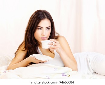 Pretty woman white dressed dink coffee in bed