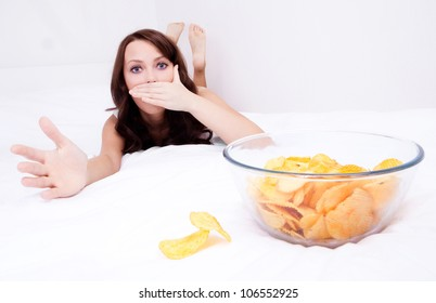 pretty woman willing to eat potato chips and scared of gaining weight,  in bed at home