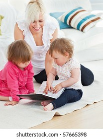 Pretty woman working with her children at laptop in living room