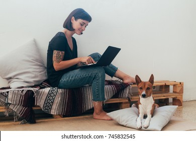 Pretty woman works from home or startup coworking space, sits barefoot on bench and writes code or blog on laptop, her best friend dog puppy lays next to her on pillow
