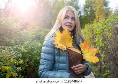 Pretty woman with yellow leaves in autumn park