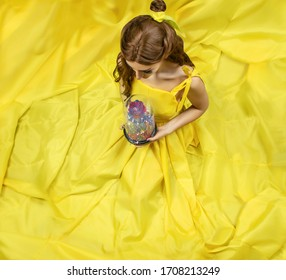 Pretty woman in the yellow long dress closeup with red rose in her hands. Beauty and the beast cosplay