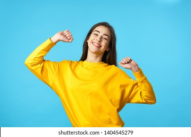 Pretty woman in a yellow sweater fun blue happiness pattern background