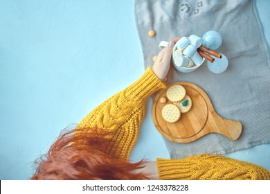 Pretty woman in a yellow sweater lying and drinking hot chocolate with marsmallows and cinnamon next to Christmas toys while decorating with cookies and miniature Christmas tree on the white table