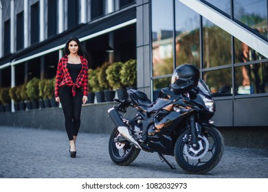 Pretty Woman! A young beautiful sexy brunette is walking around a sports motorcycle with a motorcycle helmet on the street near a modern black house. Look at the side.