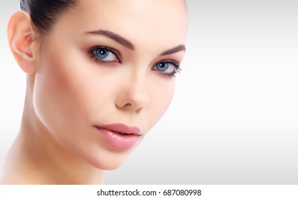 Pretty woman's face against a grey background with copyspace
