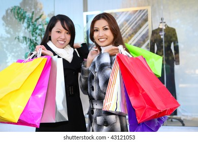 Pretty women shopping with colorful bags walking to the next store
