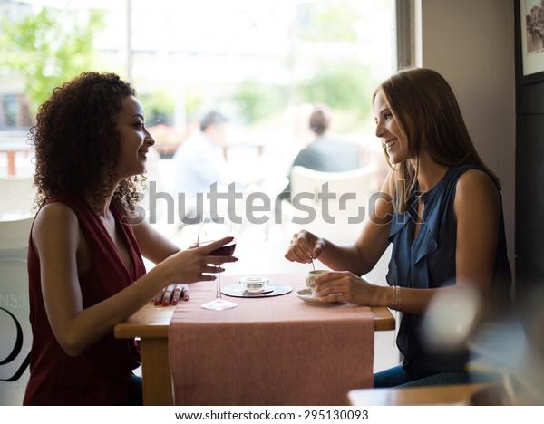 Pretty women talking and having fun inside coffee shop
