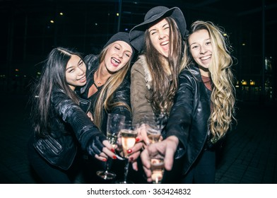 Pretty women toasting champagne glasses and having fun - Four girls drinking sparkling white wine and celebrate before going into club