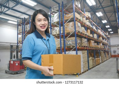 Pretty worker carrying box in the warehouse (ฺBlur background) , Asian delivery girl carrying boxes in the distribution warehouse (ฺBlur background)