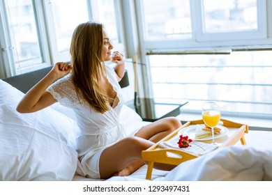 Pretty woung woman having breakfast in bed in the bedroom